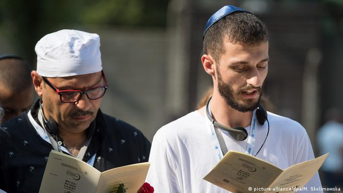 A Jew and a Muslim read out of a pamphlet on a joint visit to Auschwitz (picture-alliance/dpa/M. Skolimowska)