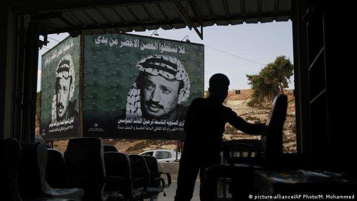 A child works at a shop across from a poster of the late Palestinian leader Yasser Arafat