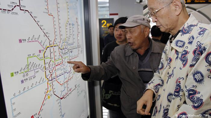 Pessoas consultam tabela com a linhas de metrô de Xangai