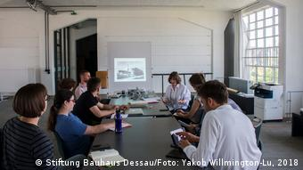 People sitting around a table with a picture projected on the wall (Stiftung Bauhaus Dessau/Photo: Yakob Willmington-Lu, 2018)