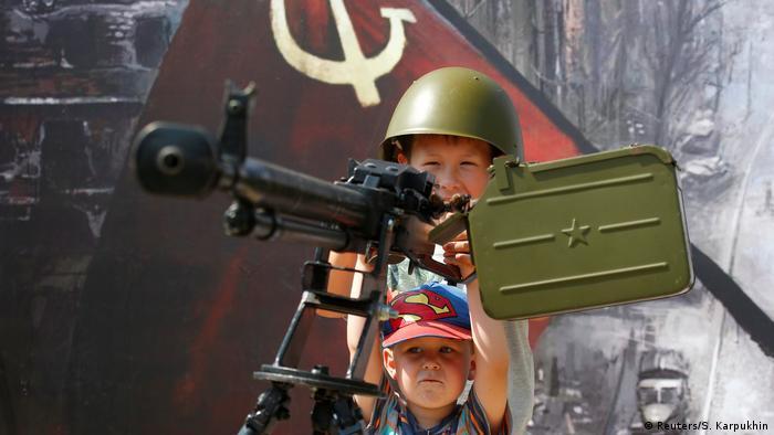 Children play with a Soviet-era machine gun (Reuters/S. Karpukhin)