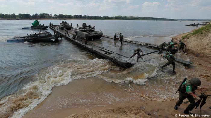 Members of the Russian team transport tanks on a pontoon bridge
