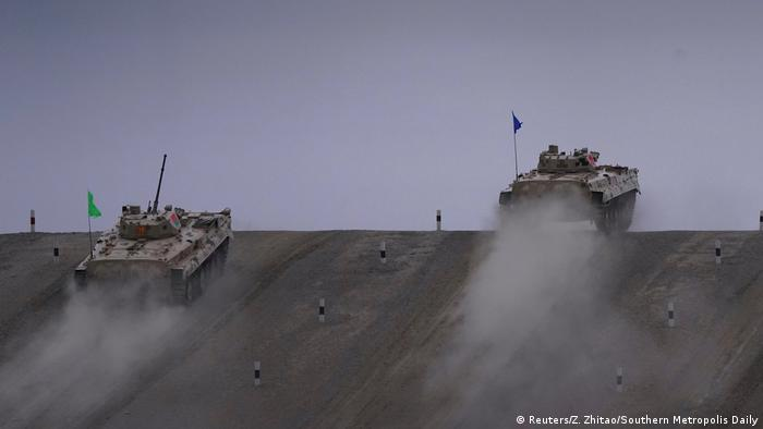 Two tanks climb a slope during the Suvorov Attack competition during the Games in Korla, Xinjiang Uighur Autonomous Region, China.