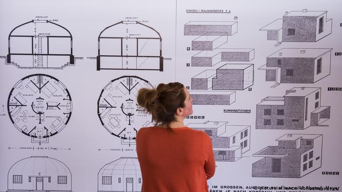 Eine Frau steht vor dem Rundhaus-Modell von Carl Fieger und dem Baukastensystem von Walter Gropius.