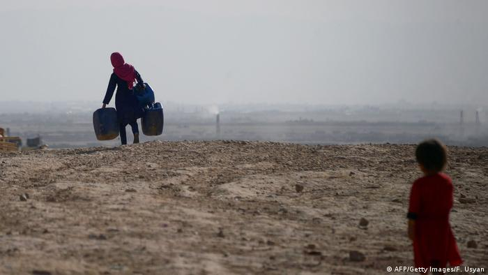 A woman carries suitcases over a dry landscape