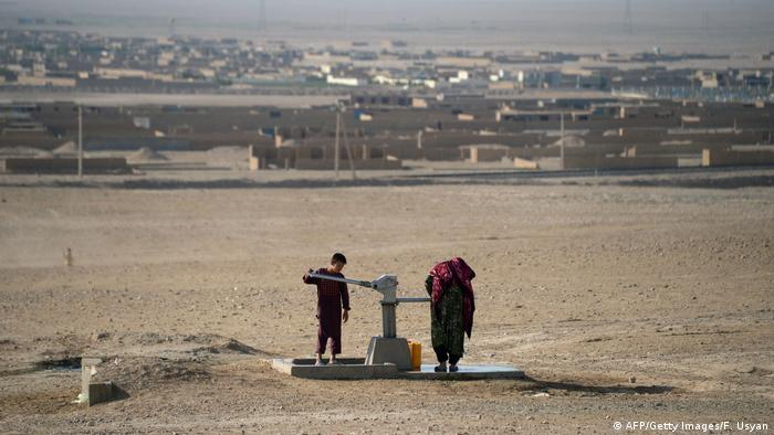 Two people stand at a water pump in the middle of a brown field