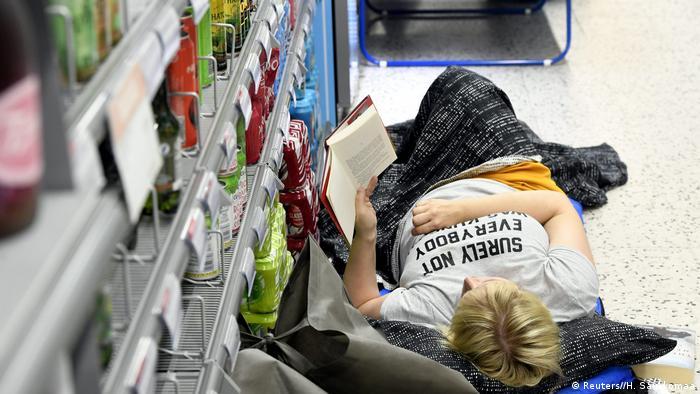 Eine Frau liegt vor einem Regal im Supermarkt und liest ein Buch (Reuters//H. Saukkomaa)
