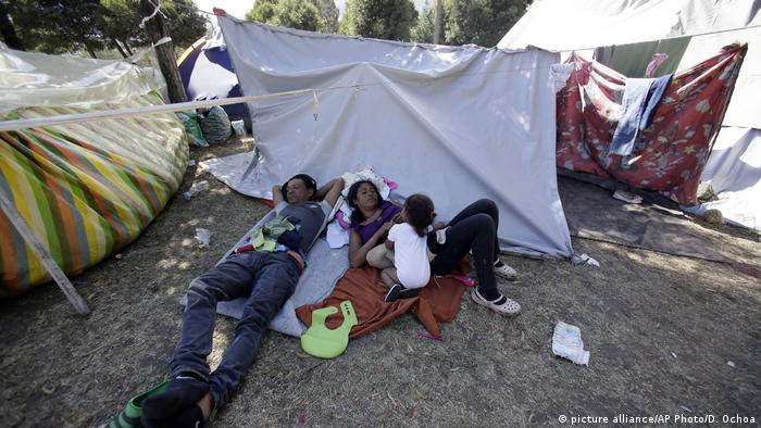 A Venezuelan family lies on blankets on the ground in a makeshift camp (picture alliance/AP Photo/D. Ochoa)