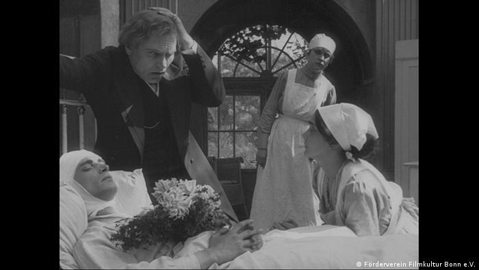 Film still of Opium, with nurses and a man standing beside a bed with a sick person in it (Förderverein Filmkultur Bonn e.V.)