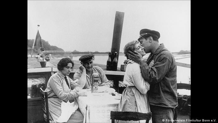 Film still , two men and two women at a table, one man kissing a woman (Förderverein Filmkultur Bonn e.V.)