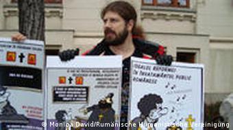 Ein Mann hält zwei Plakate hoch (Foto: Monica David/Rumänische Humanistische Vereinigung)