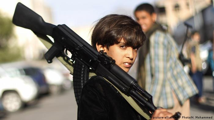 A Yemeni boy holds a weapon
