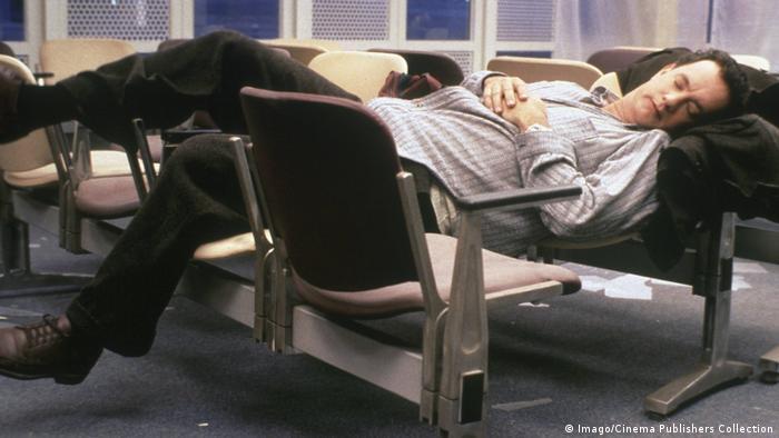 Hombre, Tom Hanks, durmiendo en un aeropuerto.