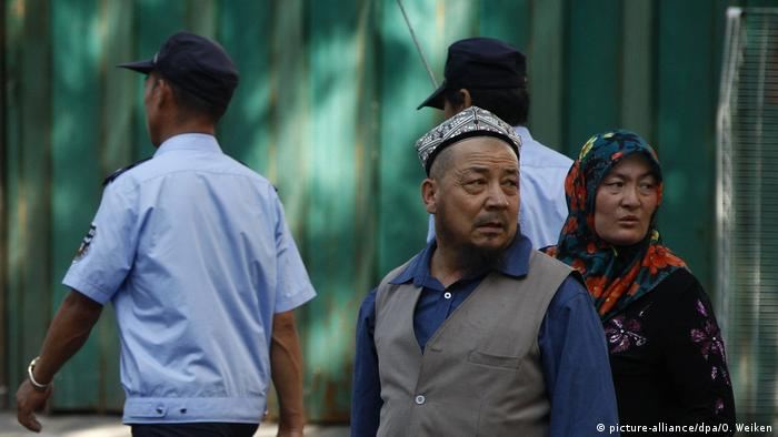 Two police men walkking past an Uyghur man and woman.