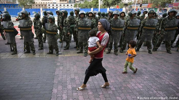 A woman walks with her two children past dozens of Chinese security personnel in Xinjiang