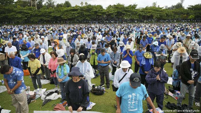 Protesters in Okinawa bow their heads in rememberance of their late-governor.