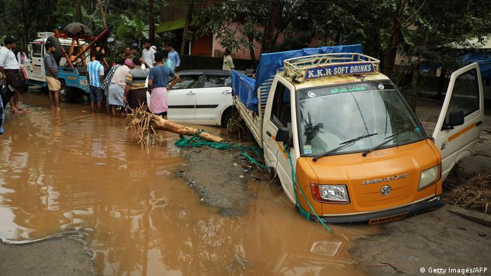 Residents look at vehicles stuck in the mud along a flooded road at Kannappankundu in Kozhikode in Kerala.
