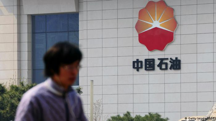 A man walks by the headquarters of the China National Petroleum Corporation in Beijing on March 25, 2015.