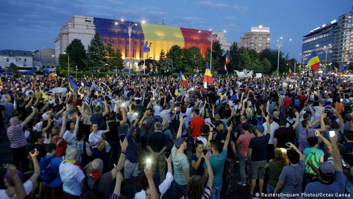 Protesters use their cell phones to shine a light on a government building in Bucharest