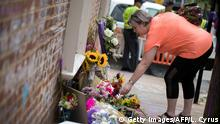 A woman places flowers at a memorial to Heather Heyer, who died in an attack on counterprotesters at a white nationalist rally in Charlottesville, Virginia (Getty Images/AFP/L. Cyrus)