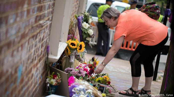 A woman places flowers at a memorial to Heather Heyer, who died in an attack on counterprotesters at a white nationalist rally in Charlottesville, Virginia