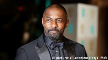 Bust shot of Idris Elba wearing a black-on-black tuxedo.