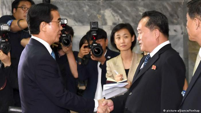 Cho Myoung-gyon and Ri Son Gwon shake hands in front of the press (picture-alliance/Yonhap)