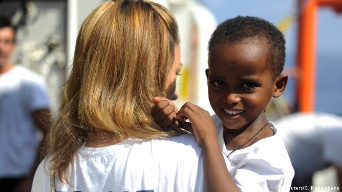 A migrant child smiles on board the MV Aquarius