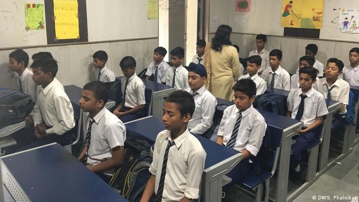 Children sit with their eyes closed in a Delhi classroom