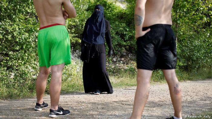 Žena u nikabu pred dva mladića u kratkim hlačama