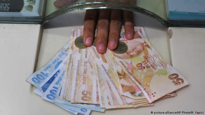 A vendor exchanges foreign currency with Turkish liras at a currency exchange shop in Istanbul