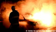 Authorities extinguish a burning car set alight by rioting youths in a Stockholm suburb in 2013 (Getty Images/AFP/J. Nackstrand)