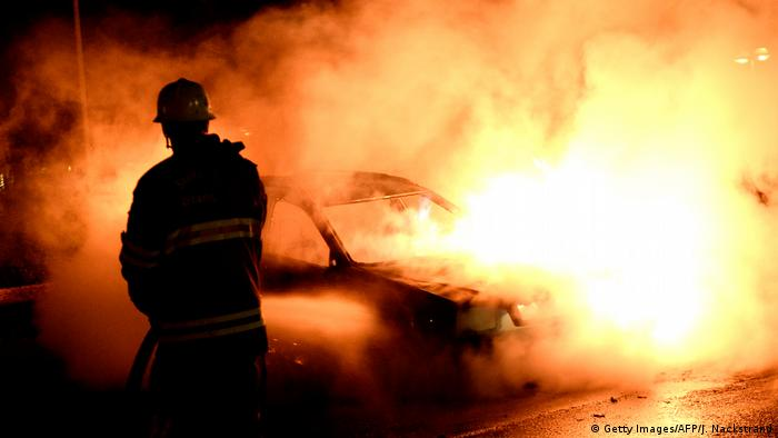 Authorities extinguish a burning car set alight by rioting youths in a Stockholm suburb in 2013
