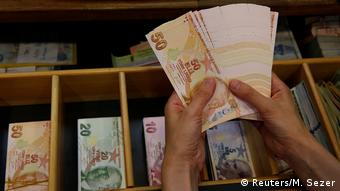 Банкноты турецкой лиры в руках у кассира
