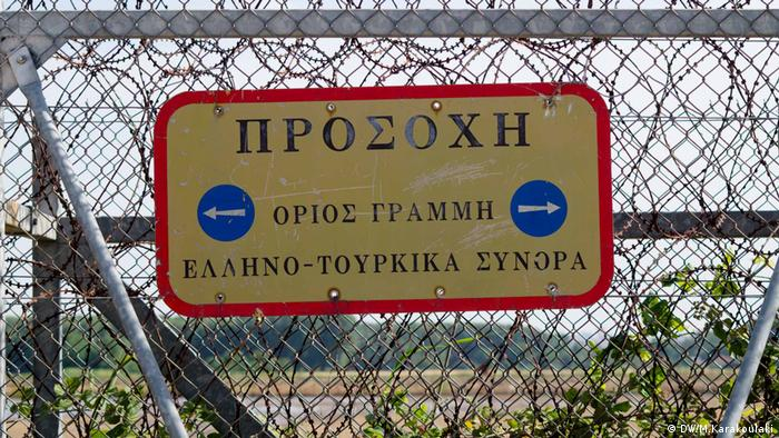 A sign on the fence that marks the Greek-Turkish land border. Sign says in Greek: 'Caution – Land border – Greek-Turkish Borders'
