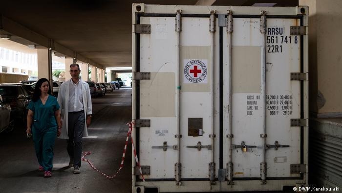 Coroner Pavlos Pavlidis and his colleague walk towards the fridge container outside the morgue (DW/M.Karakoulaki)