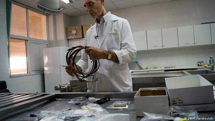 Coroner Pavlos Pavlidis holds leather belts (DW/M.Karakoulaki)