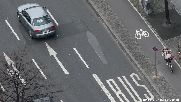 Una calle con un coche y un bus.