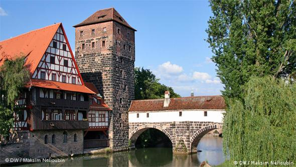 Вид на ''Мостик палача'' (Henkersteg) на реке Пегниц. В фахверковом доме слева в Средние века располагался лепрозорий, а затем винный склад. Сейчас здесь находится студенческое общежитие. ''Водная башня (''Wasserturm) была частью городской стены, построена в 1320-1325 годах. Позже в башне размещалась тюрьма. Согласно планам национал-социалистов, в 1940 году все эти здания должны были снести для строительства новой дороги, но проект не был осуществлен