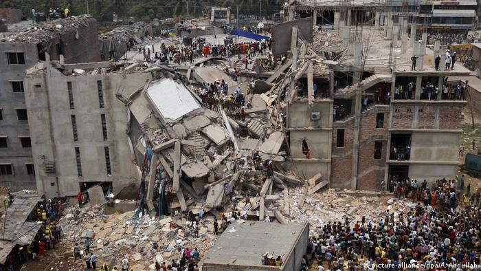 People crowd around the destroyed Rana Plaza building