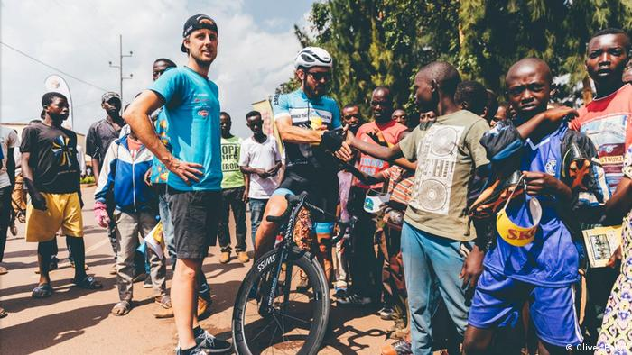 The Embrace the World team manager Micha Glowatzki (left, wearing black cap) with his rider Dan Craven and young fans at the 2018 Tour of Rwanda (Photo: Oliver Farys)