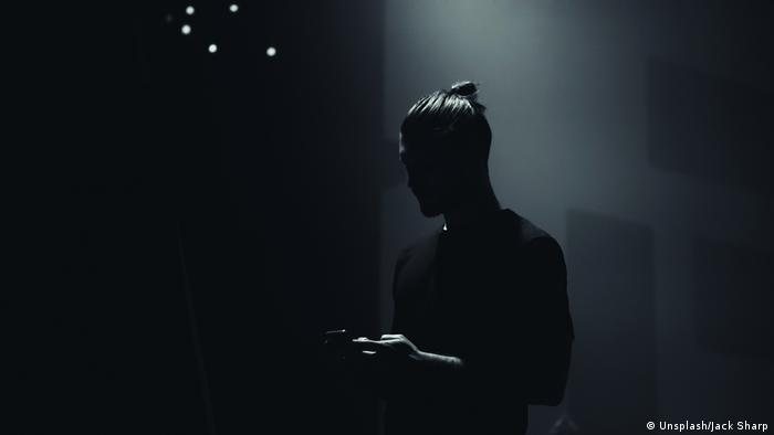 A smartphone user in the shadows