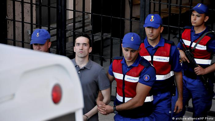 Turkish police officers escort Greek soldier Angelos Mitretodis after a court appearance