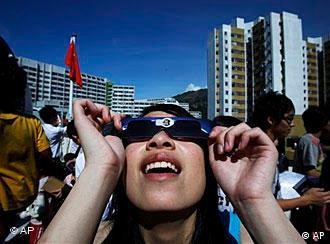 Frau in Hongkong betrachtet mit Spezialsonnenbrille die Sonnenfinsternis (Foto: AP)