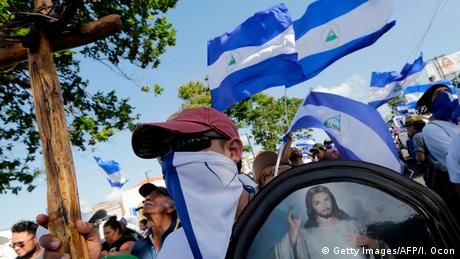 A man wearing a scarf over his mouth carries a picture of Jesus as flags wave in the background (Getty Images/AFP/I. Ocon)