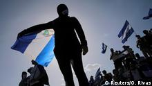 A protester holds a Nicaraguan flag (Reuters/O. Rivas)