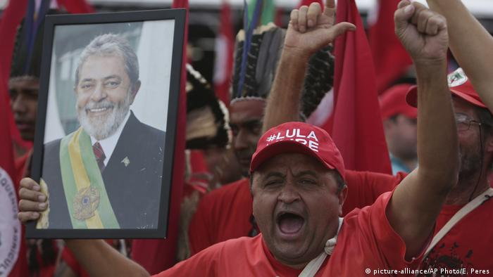 A Lula supporter at a rally holds a picture of the former president (picture-alliance/AP Photo/E. Peres)