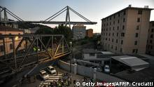 A general view shows apartment buildings under the Morandi motorway bridge in background one day after a section collapsed in Genoa