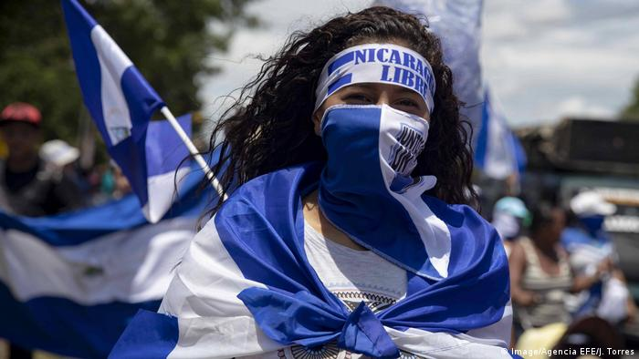 A person in a Nicaraguan flag marches wearing a headband that reads Nicaragua Libre (Image/Agencia EFE/J. Torres)