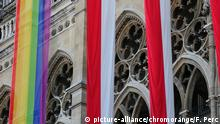 A rainbow flag and two austrian flags in Vienna (picture-alliance/chromorange/F. Perc)